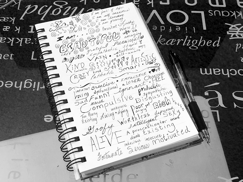 notebook on glass desk with i am affirmations handwritten on it