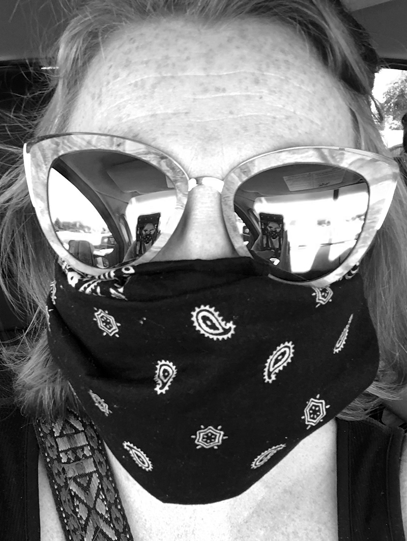 black and white selfie of a female in mirror reflective glasses and a bandana face mask