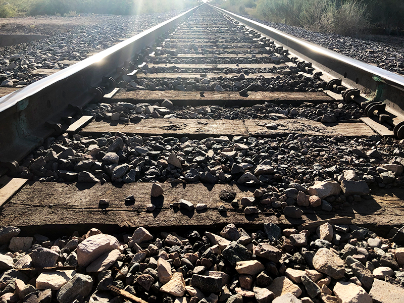 railroad tracks with the reflection of the sun on the tracks